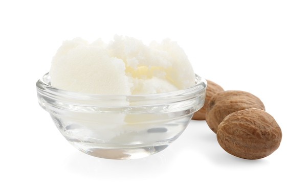 Shea butter in glass bowl and shea nuts