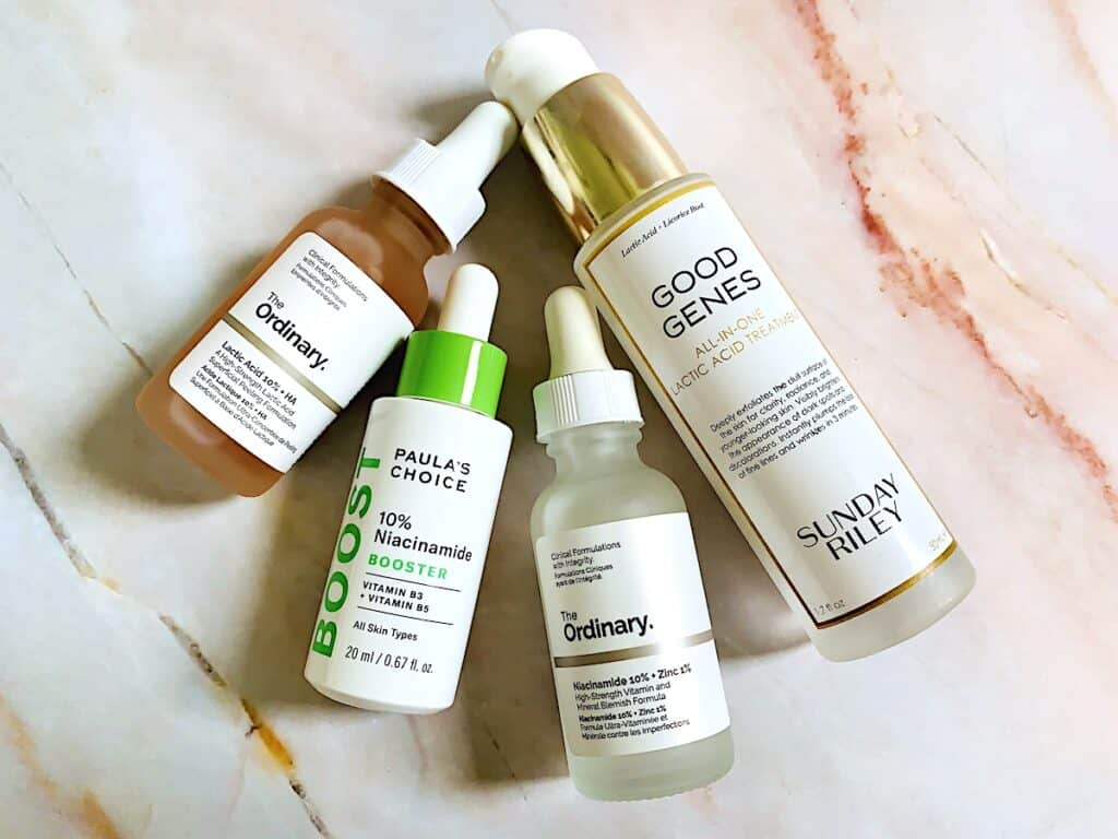 The Ordinary Niacinamide and Lactic Acid Serums, Paula's Choice 10% Niacinamide Booster, and Sunday Riley Good Genes All-In-One Lactic Acid Treatment